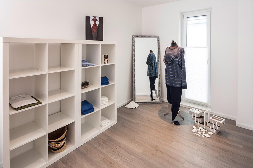 Modernes, weißes Ankleidezimmer mit dunklem, warmen Holzboden