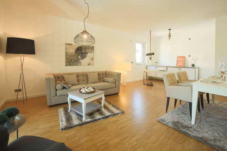 Weißes Wohnzimmer mit einem Laminatboden und weißem, sowie hellgrauem Mobiliar