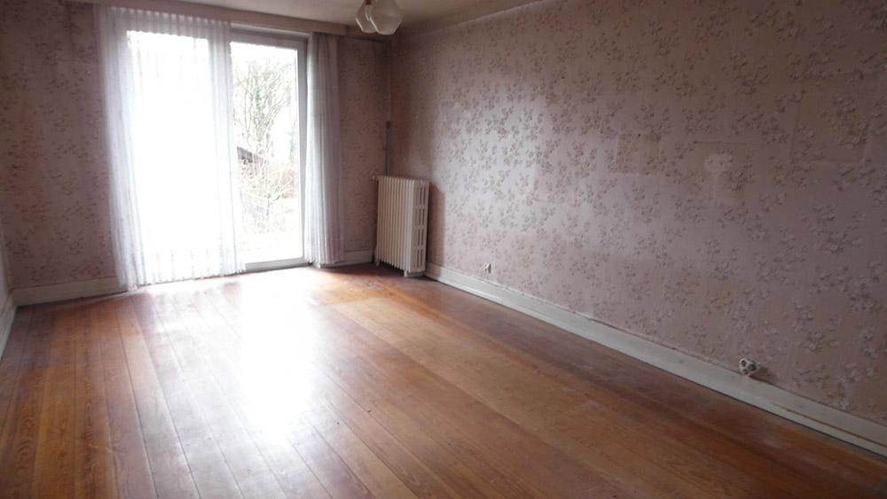 Lehrgeräumtes Wohnzimmer mit Echtholzboden und rosa-floraler Tapete