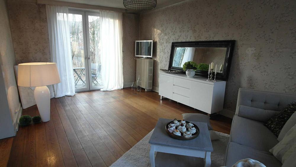 Wohnzimmer mit Echtholzboden und einer beige-floralen Tapete