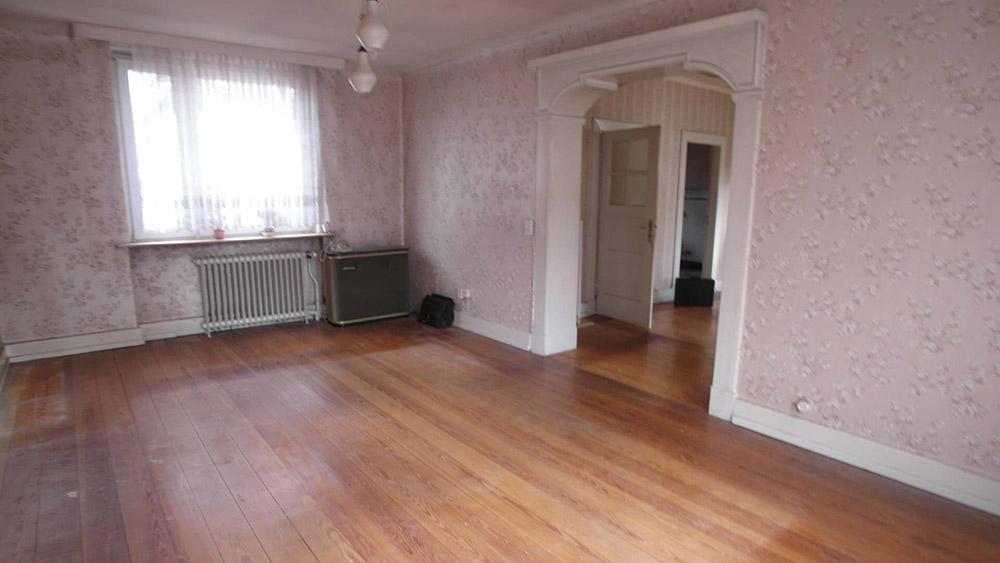 Leergeräumtes Wohnzimmer mit Echtholzboden und einer rosa-floralen Tapete