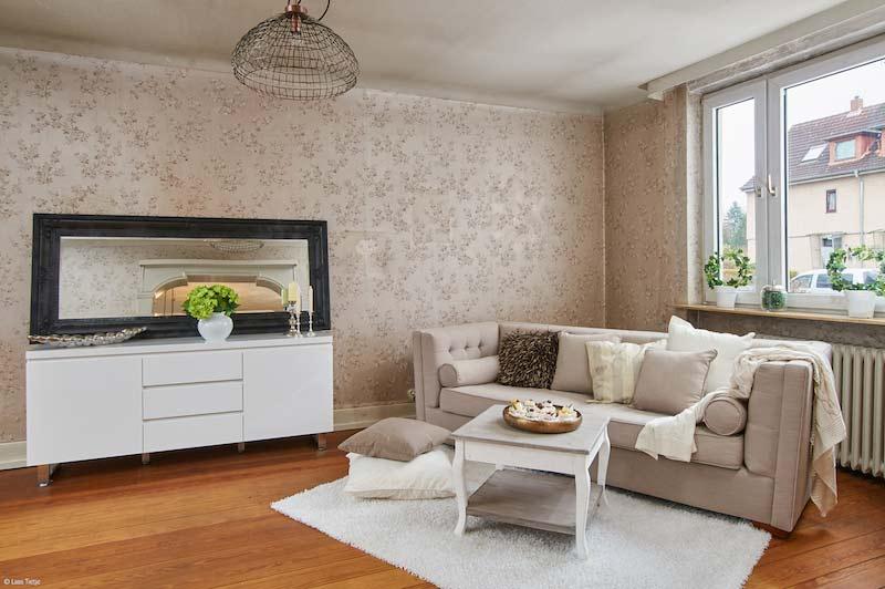 Rustikales Wohnzimmer mit Holzboden und einer floralen, beigen Tapete