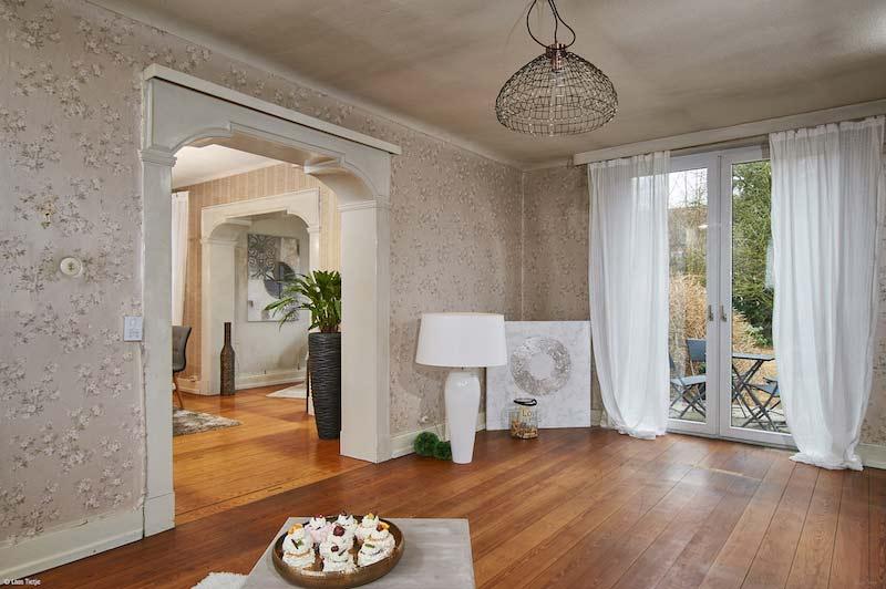 Rustikales, offenes Wohnzimmer mit Holzboden und einer altmodischen floralen Tapete