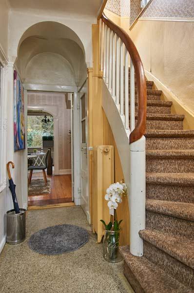 Schmales Treppenhaus in hellem Ocker mit weißem Treppengeländer und einem braunen Teppichboden