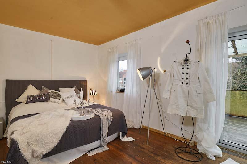 Schlafzimmer mit weißer Wand und einem Echtholzboden