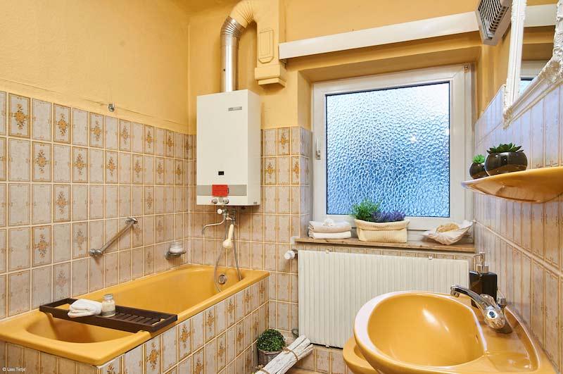 Badezimmer in Ocker mit weiß-ocker Fliesen mit einem floralen Muster