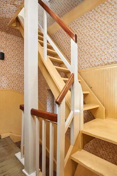 Schmales Treppenhaus in Ocker, mit weißem Geländer