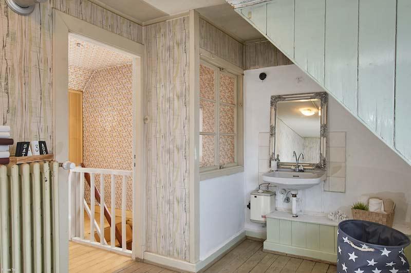 Rustikales, warmes Badezimmer mit Holzboden und hölzerner Dachschräge