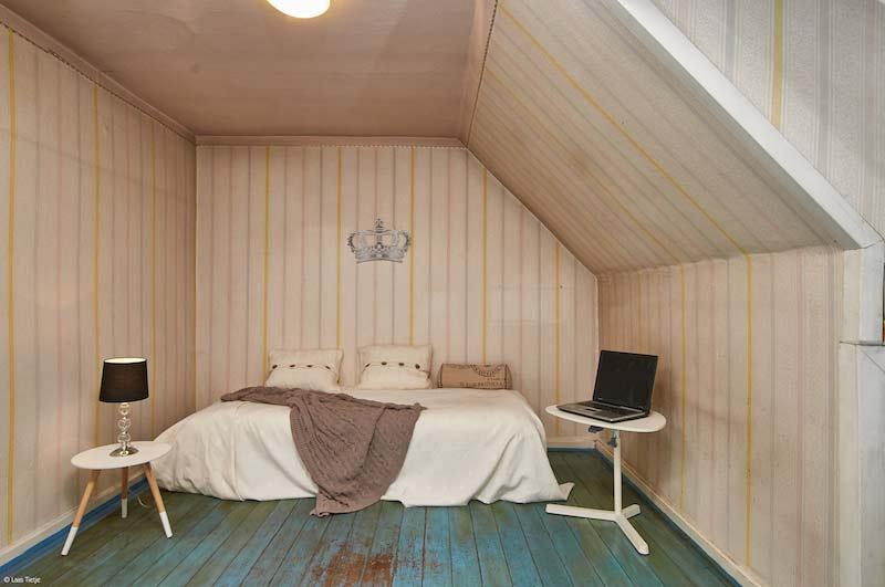 Schlafzimmer mit blauem Holzboden und weiß-gelber Nadelstreifen-Tapete