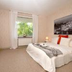 Beiges, geräumiges Schlafzimmer mit einem weißen Doppelbett