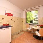 Küche mit Ocker gefliester Wand und einem Laminatboden