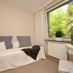 Schlafzimmer in hellem Beige mit einem geräumigen Bett und großem Fenster