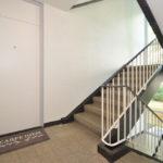 Ein Treppenhaus mit beigem Boden und weißen Wänden